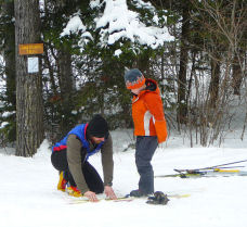 Learning how to put on a ski -- ski lessons
